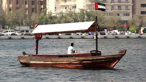 Abra driver sit on vessel bench, boat drift in middle of water, Dubai Creek Footage