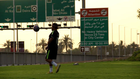 Man train freestyle football, hold ball in air using legs and feet kicks Footage