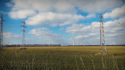 Vehicle long shot of wind farm park and power grid lines and poles green grass Footage