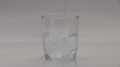 1080p Ungraded: Pouring Water Into Transparent Glass on White Background Footage