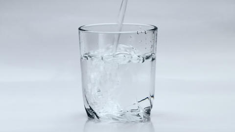 1080p Pouring Water Into Transparent Glass on White Background Footage
