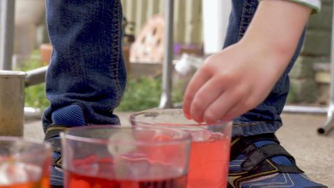 Close up of two young children coloring and dyeing easter eggs together outside Footage