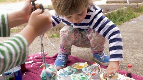 Adorable young boy and girl making colorful arts and crafts project outside in Footage