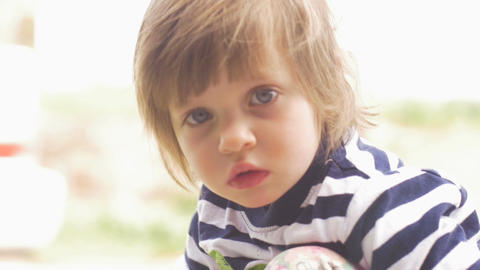 Worried serious adorable cute little girl looking at the camera sitting outside Footage
