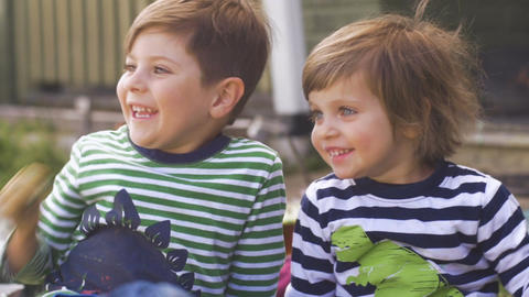Two excited young children sitting, smiling and looking in anticipation outside Footage