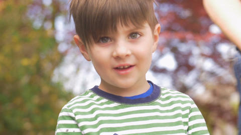Portrait of an attractive adorable happy smiling little boy in slow motion Footage