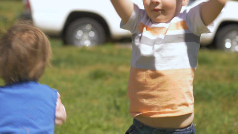 Two happy smiling young children jumping and playing together outside having fun Footage