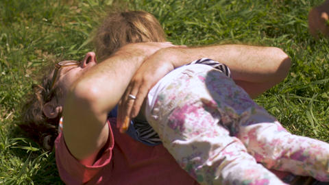 Two young children hugging their dad while wrestling on the grass in slow motion Footage