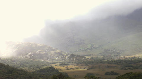 Light rays pierce the clouds and fog and shine on rocks in a valley Footage