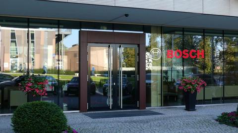 Glass facade of a modern office building with Robert Bosch GmbH logo. Editorial Live Action