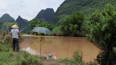 River And Man Fishing For Hobby Near Yangshuo In China Footage