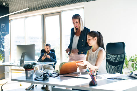 Three business people in the office working together Photo