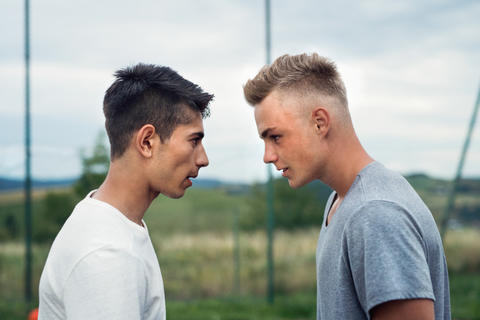 Two boys on playground looking at each other with hate Photo