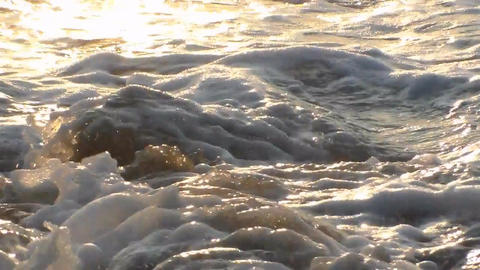 Waves beat against the rocks on the shore of the sea, the sea at sunset Footage