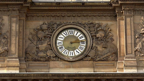 Clock in facade of Louvre Museum in Paris. France Live Action