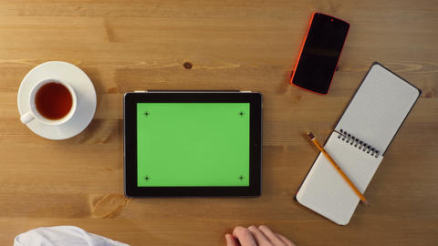 Using Tablet PC with a Green Screen on a Wooden Desktop Live Action
