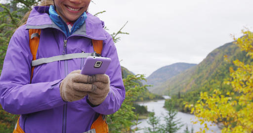 Woman using phone app in nature hiking in fall using smartphone Footage