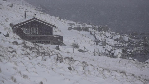House on the Rocky Shore of the Fjord and Snowfall. Slow Motion. Looped Footage