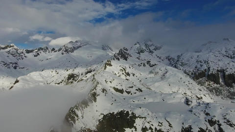 Flying over snow-capped mountains in clouds Footage