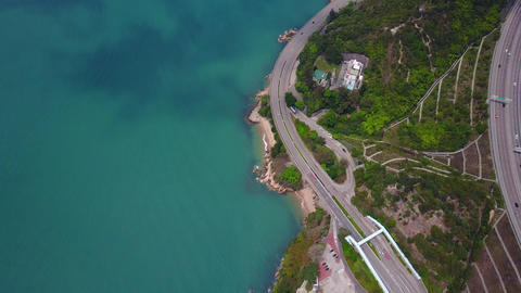 Fly over Castle Peak Road along shore, camera tilt up from top-down view Footage