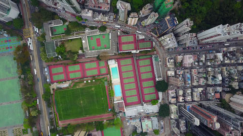 Aerial top-down shot from Causeway Bay Sports Ground to green hill slope Footage