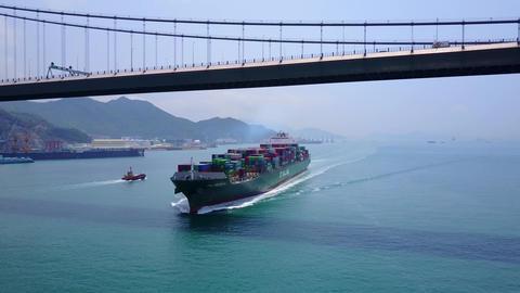 Large containership pass under big suspension bridge, aerial shot Footage