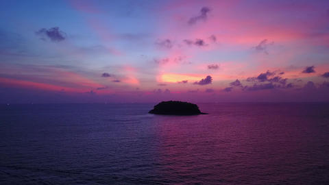 Neat pink tint of sunset sky, tropical island at sea, aerial shot Footage