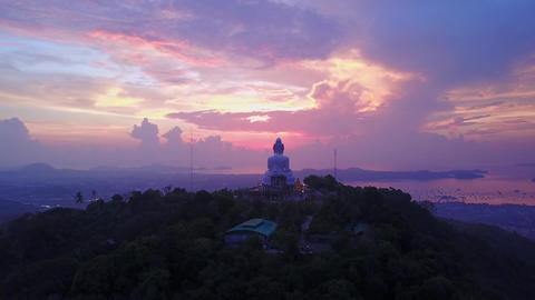 Large Buddha statue on hill summit against fascinating clouds at sunrise time Footage