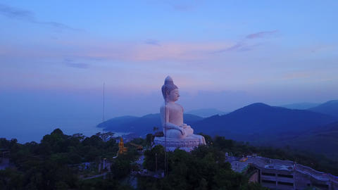 Big Buddha statue on top of hill, aerial orbiting shot at early morning hour Footage