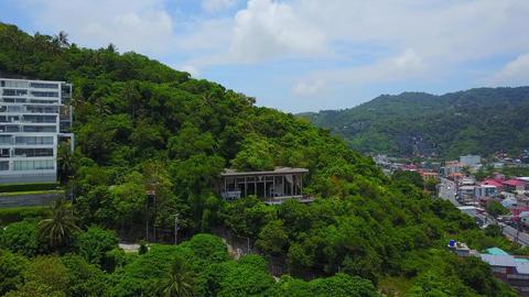 Abandoned pavilion-like building at wooded hillside, buried in verdure Footage