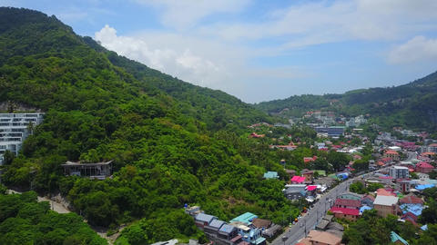 Large village area at bottom of green forested hill, aerial panorama of Kata Footage