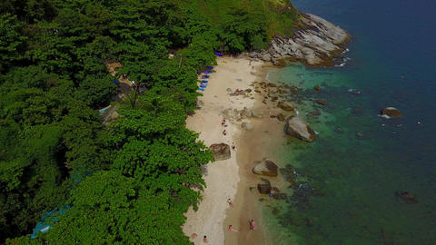 Exotic beach under green canopy of trees, large stones in water, rocky cape Footage