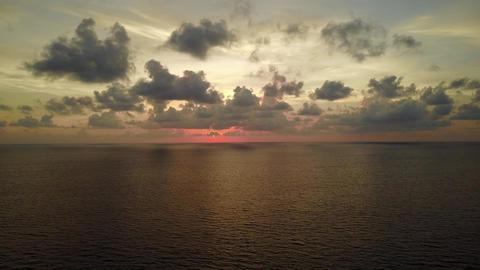 Tender red glow of setting sun over sea horizon line, dark cumulus clouds Footage