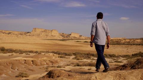 Jib shot of man walking into the desert Desolation Live Action