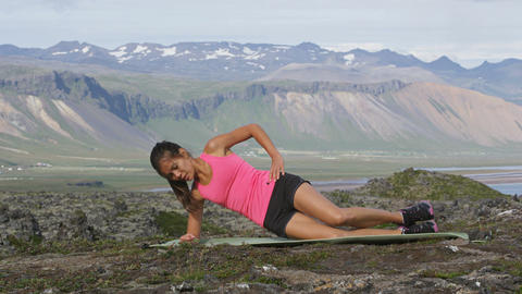 Fitness woman doing core strength exercise for abs and obliques outside Footage