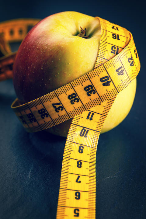 apple with yellow measuring tape Photo