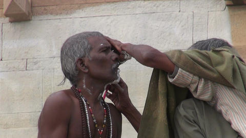 indian street barber shaving hindu brahman monk using an open razor blade on a Footage