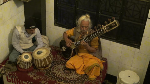 two indian musicians playing with instruments in German bakery restaurant, Live Action