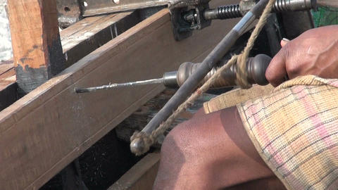 master with primitive tool drilling wooden boat near Ganges river, Varanasi Live Action