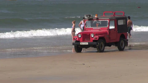 red lifeguard jeep vehicle on sandy resort beach and peoples, Goa, India Footage