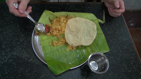 tourist eating vegetarian rice with tomato on banana leaf in south India Live Action