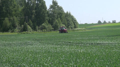 Tractor spraying field with sprayer, herbicides, pesticides and fertilizer Live Action