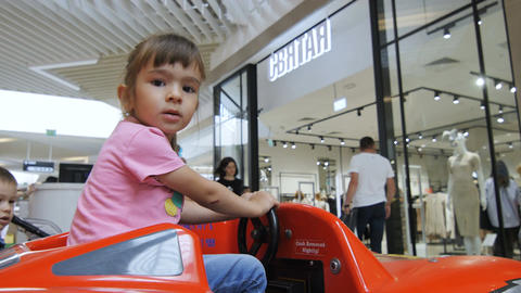 Closeup Little Girl Sits in Toy Car in Mall Hall among People Footage