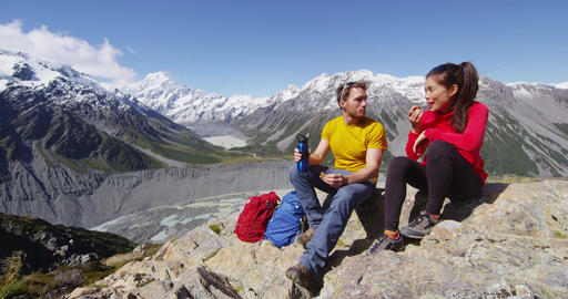 Hiking couple taking food break on alpine hike in New Zealand by Mount Cook Live Action