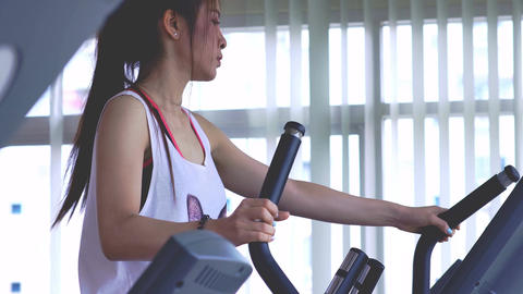 Young Woman Exercising on the Cross Trainer Machine Image