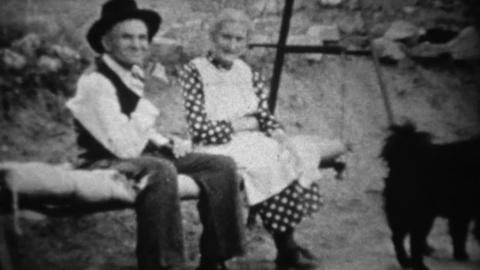 1939: Grandparents rocking on porch swing with black dog Footage