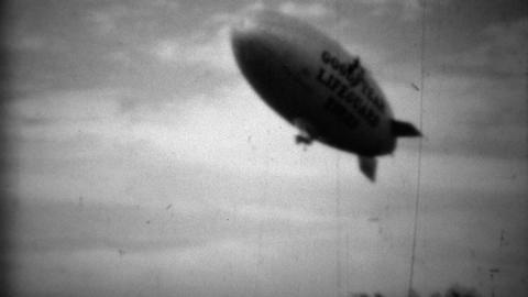 1938: Goodyear Lifeguard Tire Blimp Flying Above Classic Car stock footage