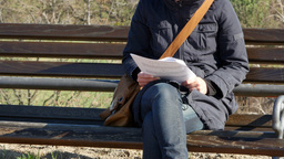 ZOOM OUT On A Young Woman Reading On The Park Bench stock footage