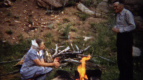 1940: Couple warming up by campfire in formal fashion dress Footage