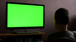 child (young boy) watches television - child plays with a TV controller - green  Footage